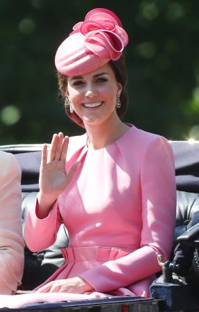 In een zuurstokroze jurk van Alexander McQueen met hoed van Jane Taylor en oorbellen in bruikleen van koningin Elizabeth II