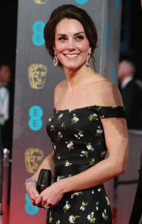In een zwarte off-shoulderjurk met bloemenprint met zwarte clutch, beide van Alexander McQueen, en juwelen in bruikleen van koningin Elizabeth II
