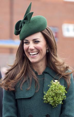 In een smaragdgroene mantel van Hobbs met hoed van Gina Foster en oorbellen van Kiki McDonough