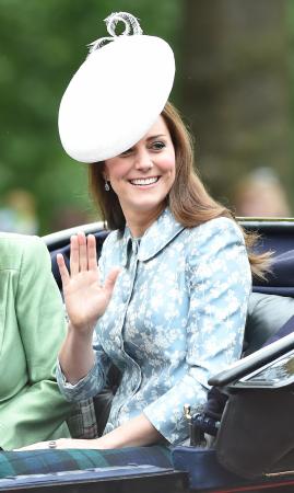 In een ijsblauwe mantel met bloemenprint vanCatherine Walker met hoed vanLock & Co