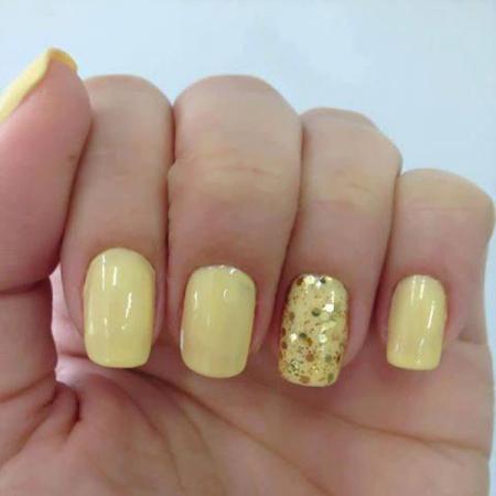 Gele pastelnagels met gouden glitters