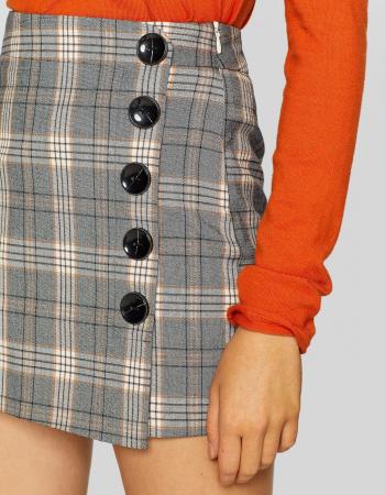 Grijze rok met witte en oranje ruiten en knopen