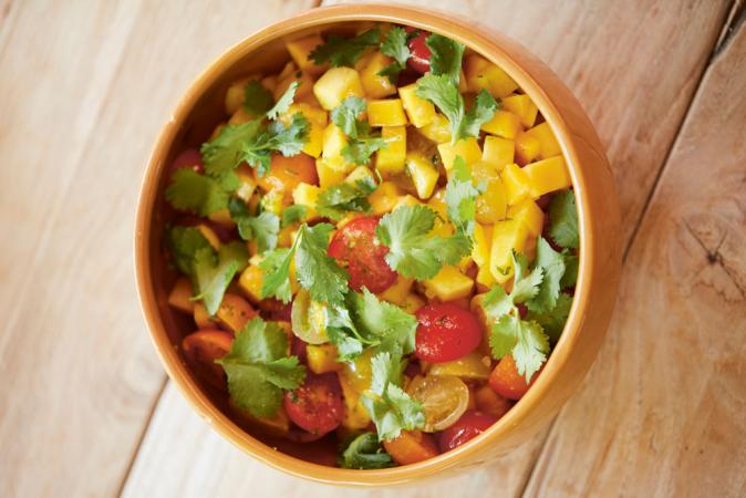 Op het vel gebakken zeebaars met mango, tomaat, chilien gember