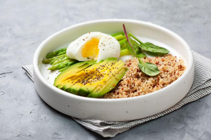 Quinoabowl met verse spinazie, avocado en een gepocheerd ei