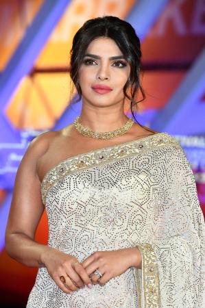 Nonchalant opsteekkapsel met krullen zoals Pryanka Chopra