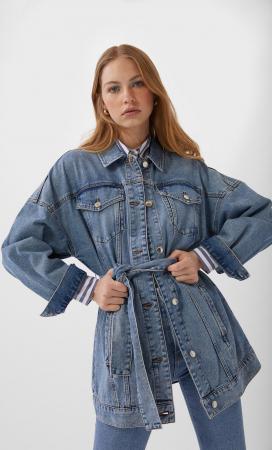 Une longue veste en jean à ceinture