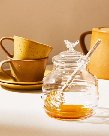 Glazen honingpotje met lepel