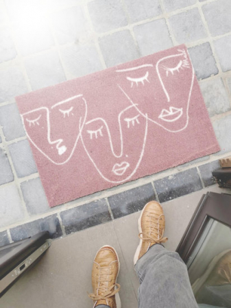 Roze deurmat met geïllustreerde gezichten
