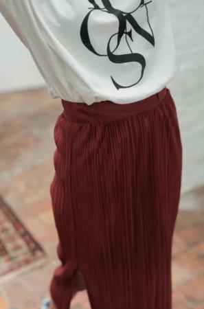 Une jupe bordeaux et plissée