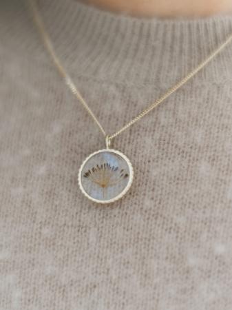 Amulet uit 14 k goud metgedroogde bloem in hars vervat
