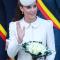 In een crèmekleurige mantel van Alexander McQueen met hoed van Jane Taylor, oorbellen van Kiki McDonough en clutch van Alexander McQueen