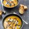 Soep van rode linzen en kurkuma met geroosterde pompoenpitten