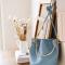 Lichtblauwe tas met gouden handvat