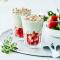 Glaasjes met wittechocolademousse met matcha, aardbeien en cashewnoten