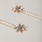 Set van twee goudkleurige haarspelden met strasbloemen