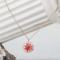 Amulette avec fleur séchée contenue dans de la résine