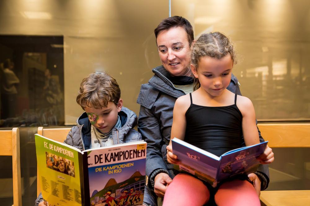 Jente is helemaal verdiept in haar Kampioenen-strip. Ook zus Tiebe kruipt na de balletles nog even bij mama Lies Vanhaecke op de schoot met een boek. (Foto's Davy Coghe)