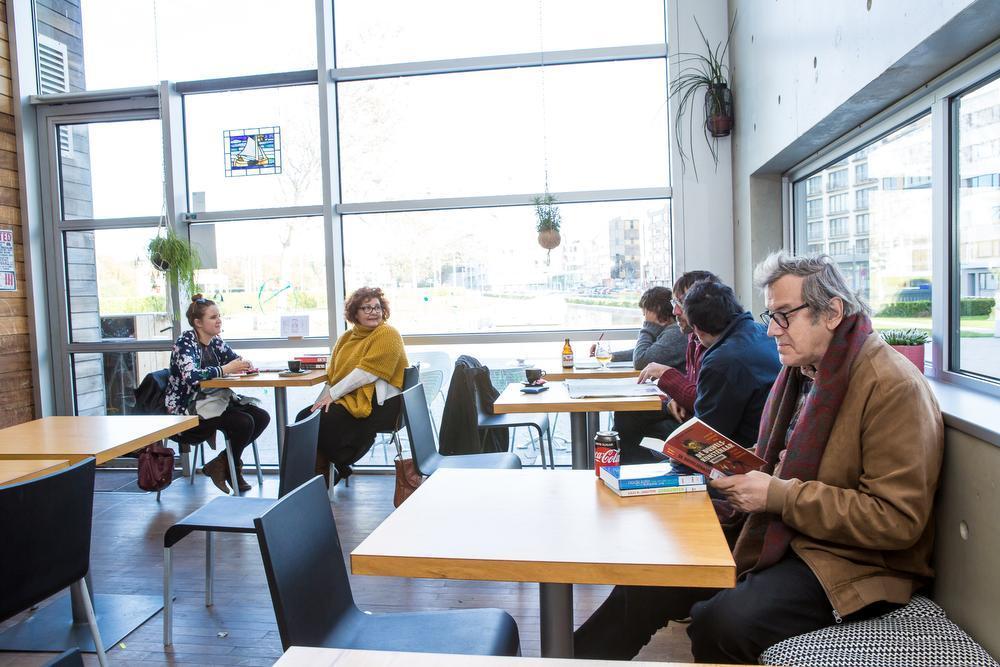 In het leescafé in Oostende verdiept Eric Rosseel (rechts vooraan) zich in een boek. Op de achtergrond slaan mensen een praatje of lezen de krant.