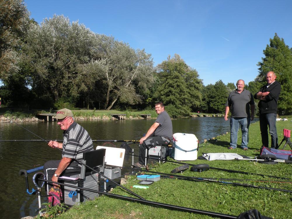Gervais Debrulle, Christophe Legley, Patrick Noppe en Ivan Dufromont genieten van de rust langs de vijver.