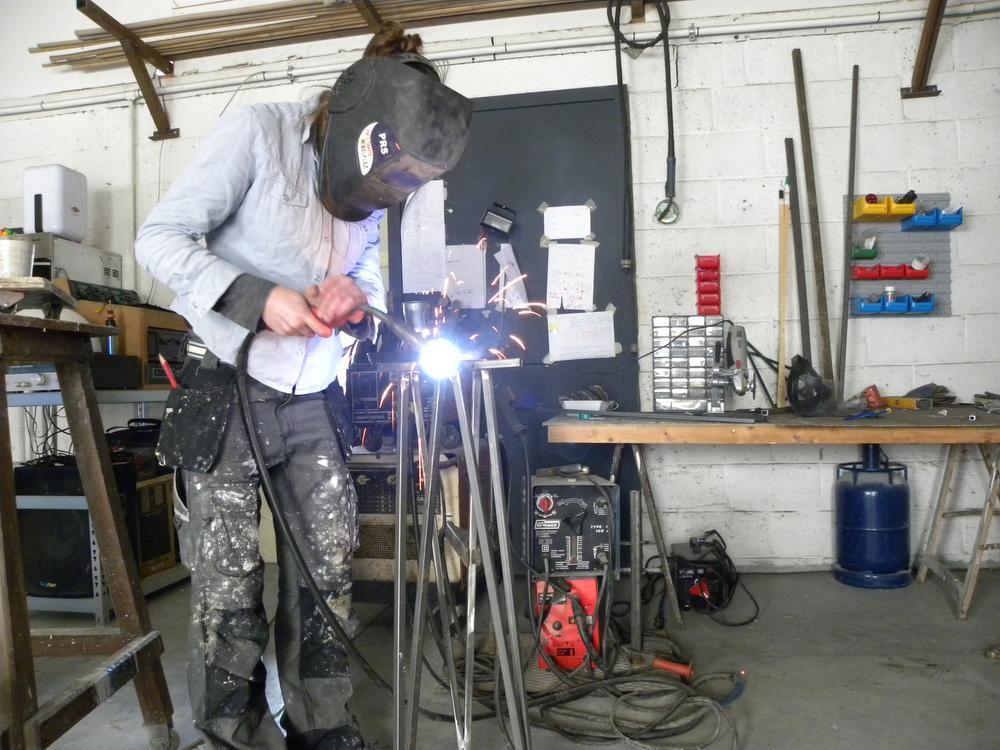 Het werk in het atelier is vaak 'mannenwerk'. Hier last Nel een sokkel.