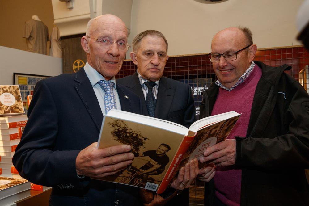 Eric Leman (links) leest gretig in het boek. Freddy Maertens en Michel Pollentier kijken toe.