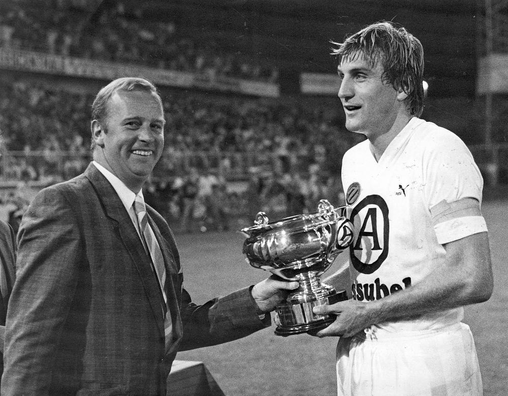Jan Ceulemans krijgt in de zomer van 1986 na winst in Anderlecht de Supercup uit handen van toenmalig bondsvoorzitter Michel D'Hooghe. De Brugse arts had ooit een hond die Caje heette, maar sinds het trainersontslag van Ceulemans bij Club Brugge zijn beide heren niet meer on speaking terms.