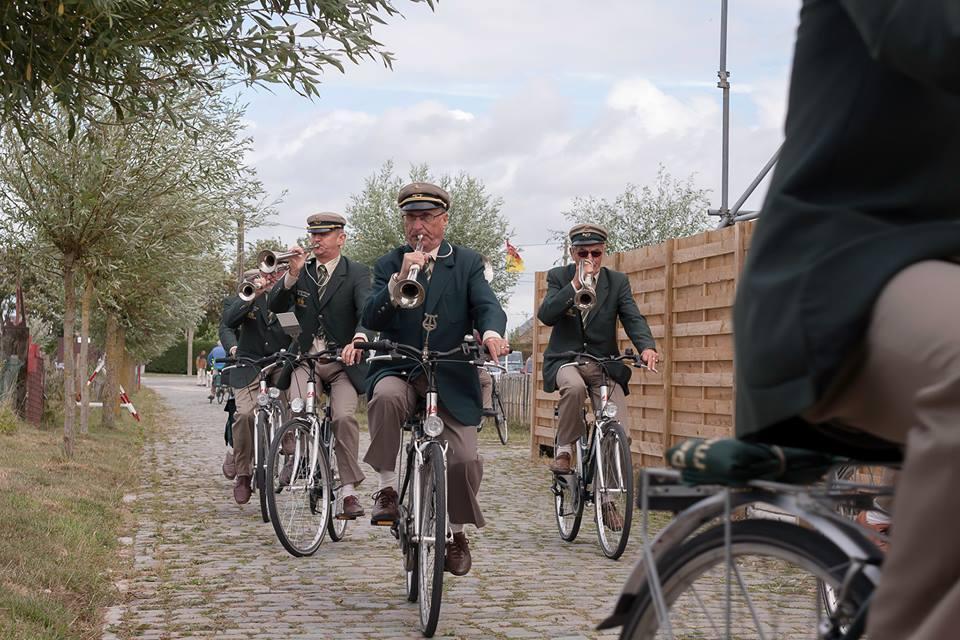 De fietsende fanfare komt erbij in Waregem.