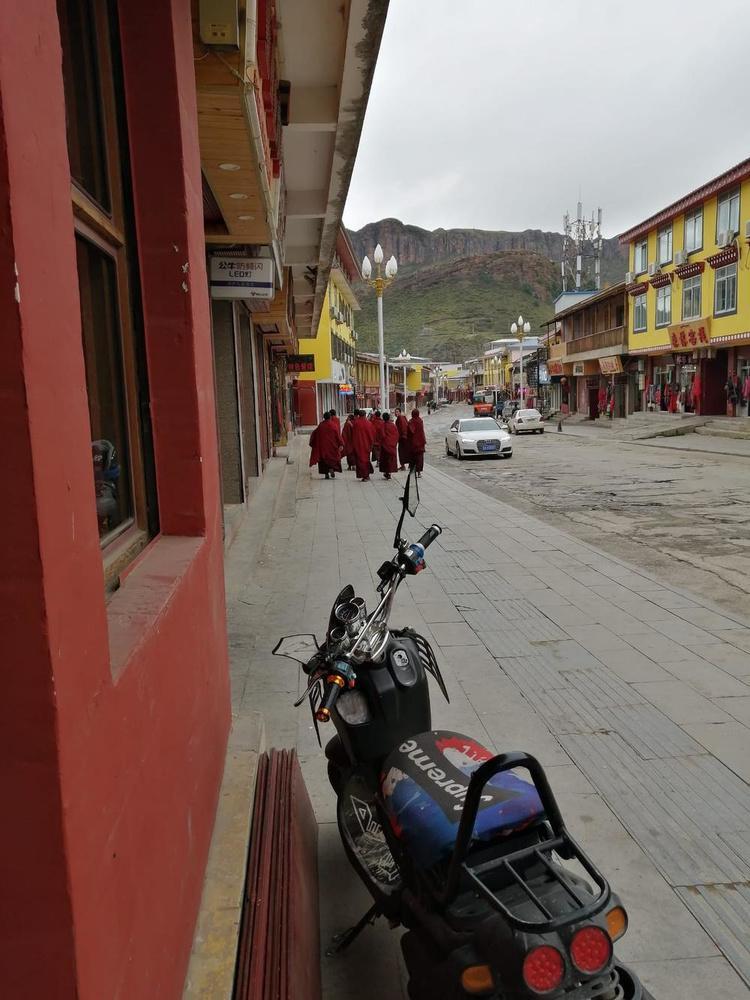 Foto 1 en 3 - leerlingmonniken op straat en spelende leerlingmonniken in Langmusi