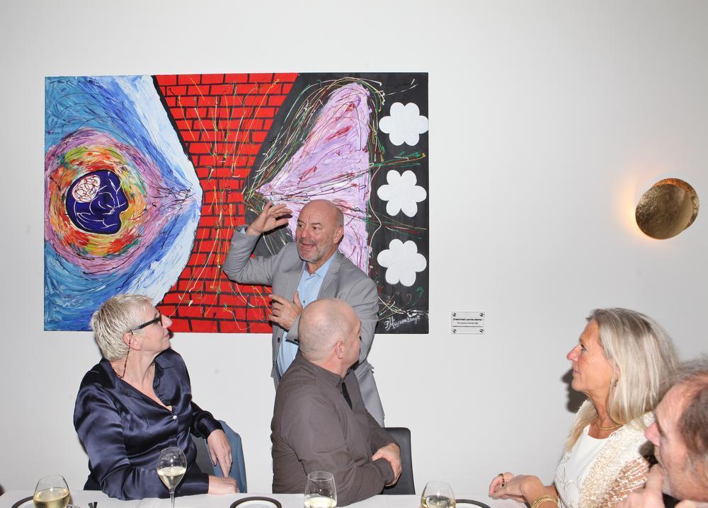 Piet Huysentruyt bij zijn schilderij, dat hij toelicht voor de restaurantgasten.