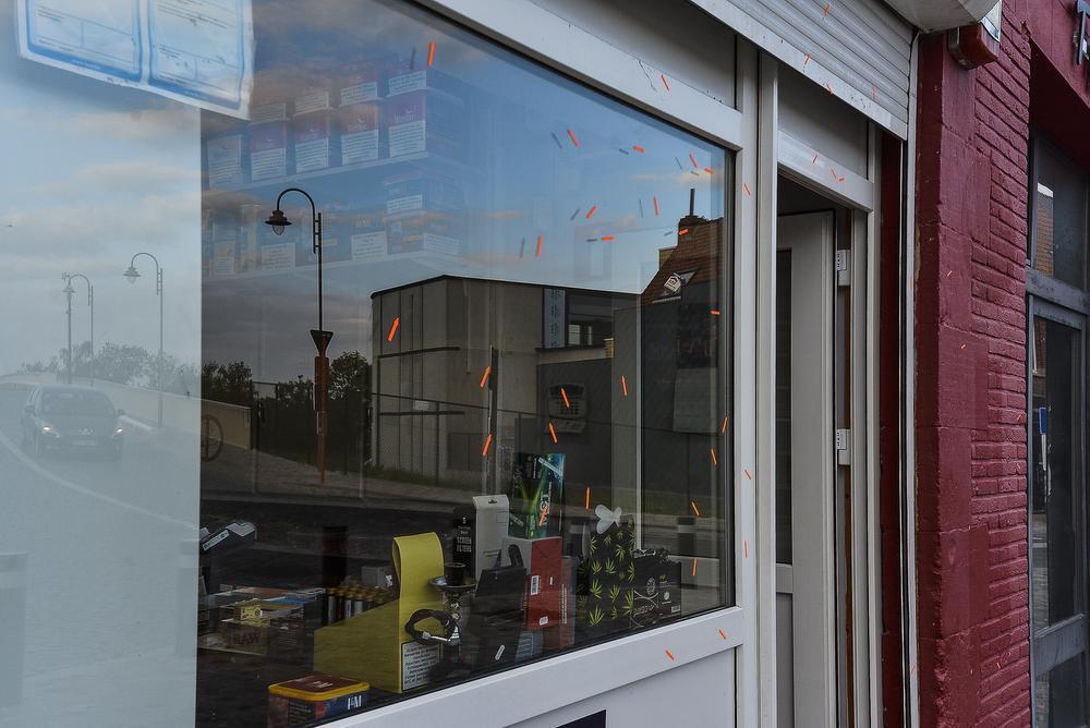 De verschillende inslagen van hagel op het raam en rolluik van de nachtwinkel werden met oranje pijltjes aangeduid.