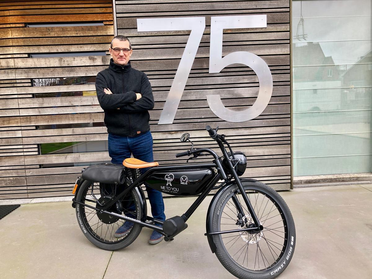 Koen Vandewalle poseert met zijn hippe, zwarte elektrische retro-motorfiets.