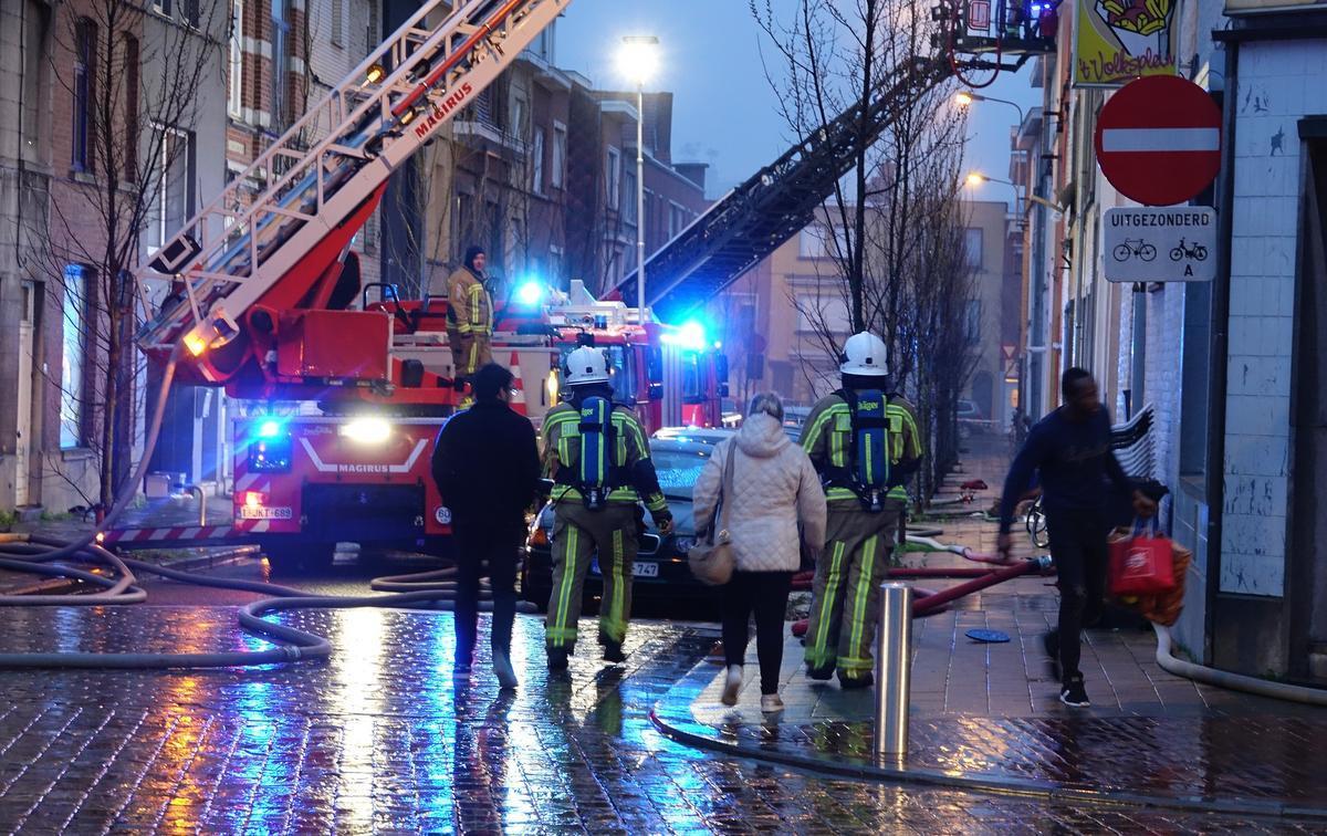 Enkele buurtbewoners mogen onder begeleiding van de brandweer de huizen betreden in de straat de niet getroffen werden door de brand.