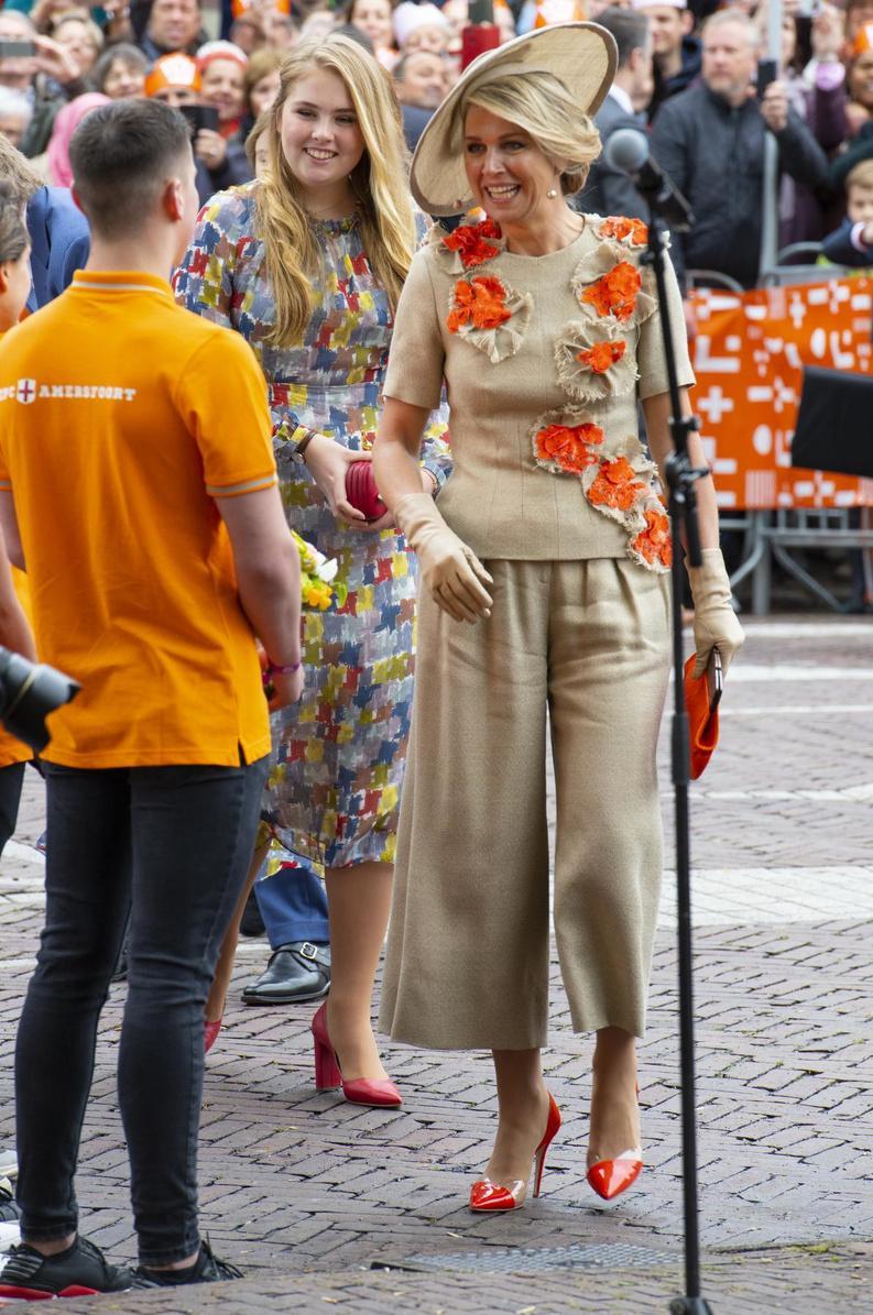 De oranje accessoires geven de discrete beige outfit van koningin Maxima pit.
