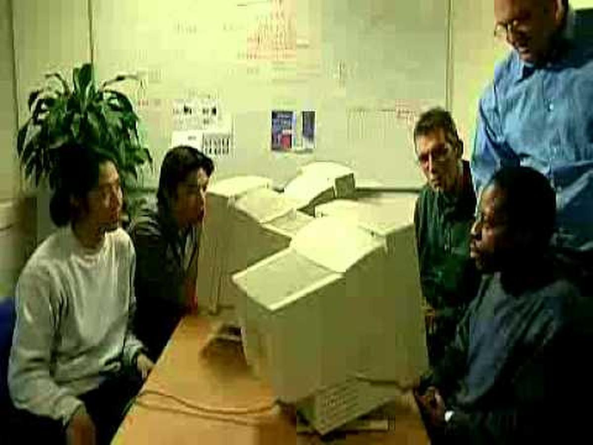 Gilbert Nyatanyi als 'Gilberke' in de iconische sketch 'Rutte 98', geflankeerd door Rob Vanoudenhoven en Wim Opbrouck.