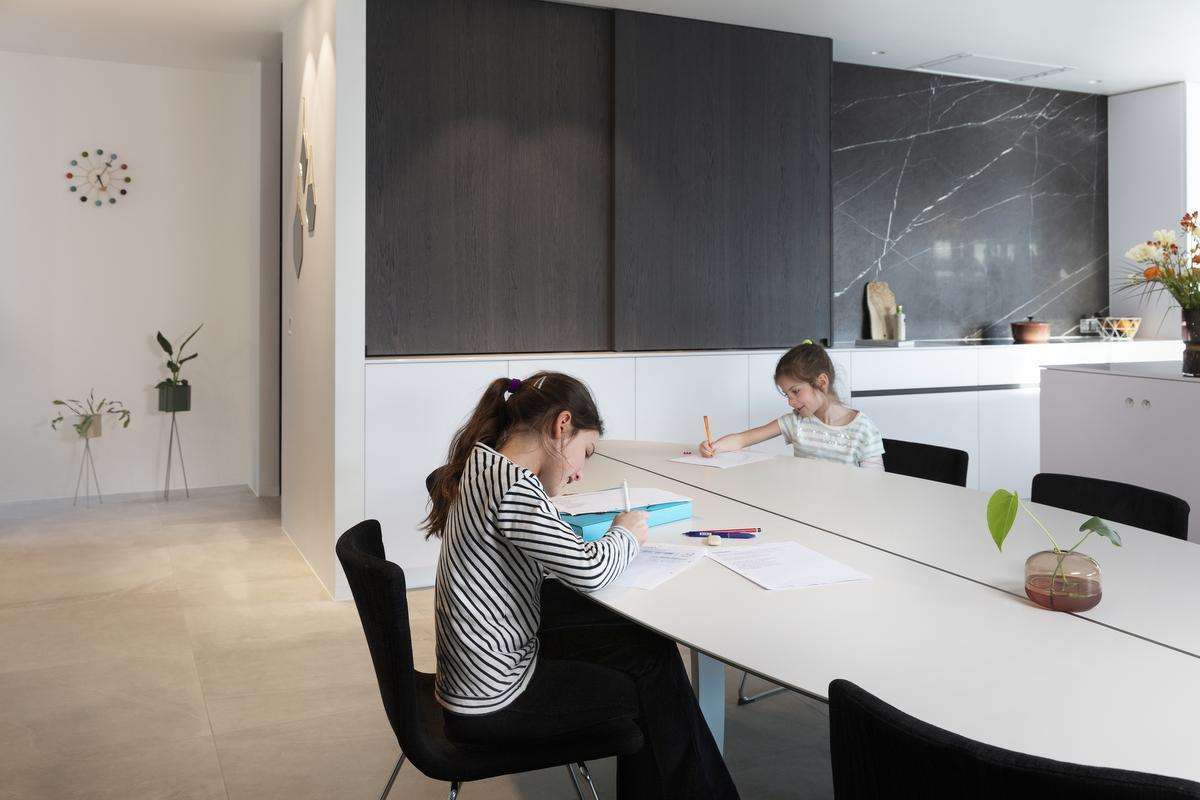 Keuken en woonruimte vloeien in elkaar over en bieden ook ruimte aan de kinderen.