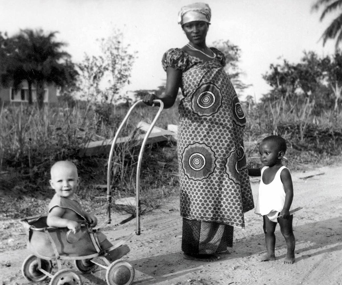 De zwangere vrouw van een boy met een kind van een koloniaal gezin in de kinderwagen. Voor haar eigen zoontje is er geen kinderwagen.
