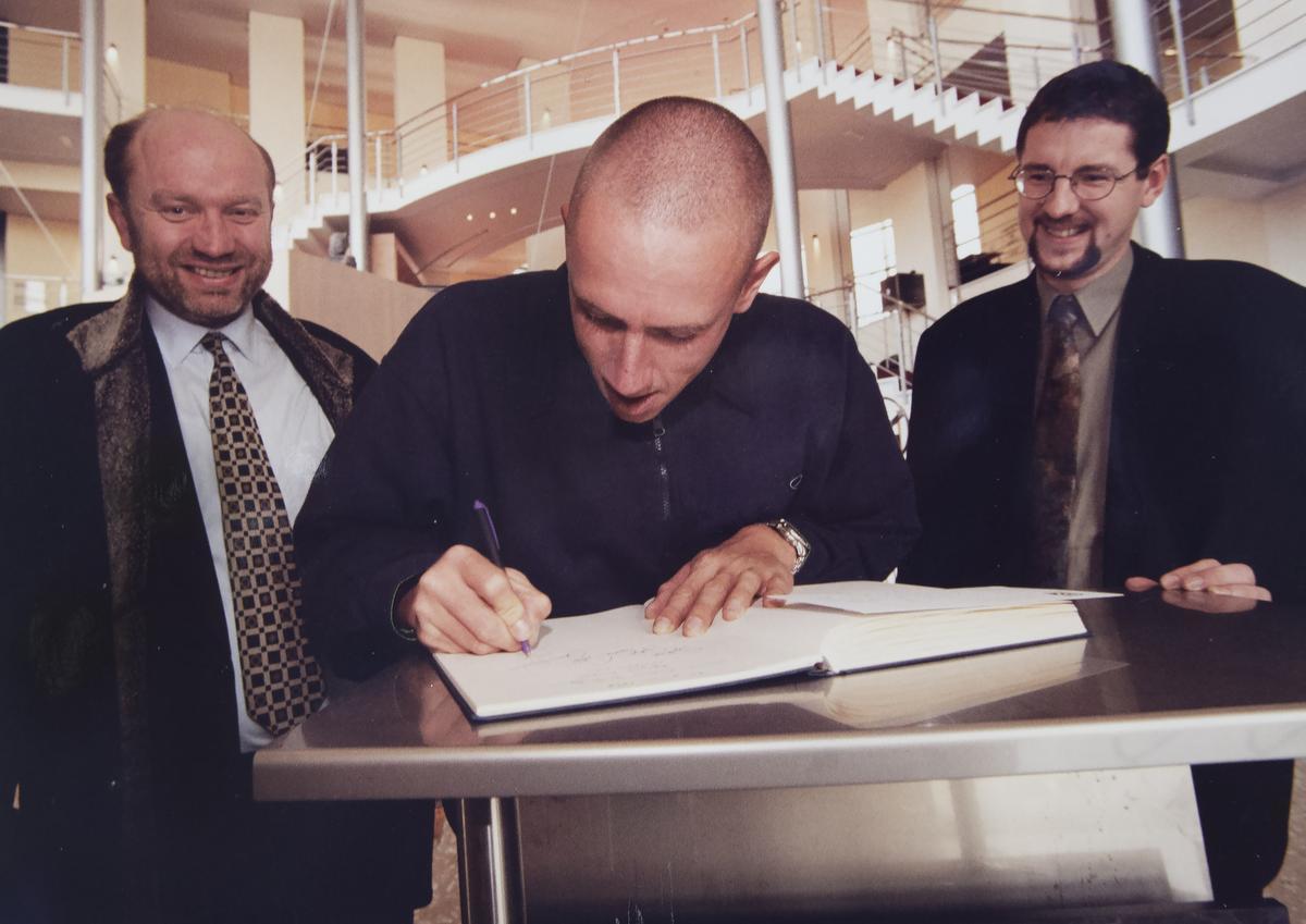 VMS-directeur Willy Phlypo en Spil-directeur Filip Strobbe kijken hoe VMS-leerling en olympisch kampioen Fred Deburghgraeve het gulden boek signeert.