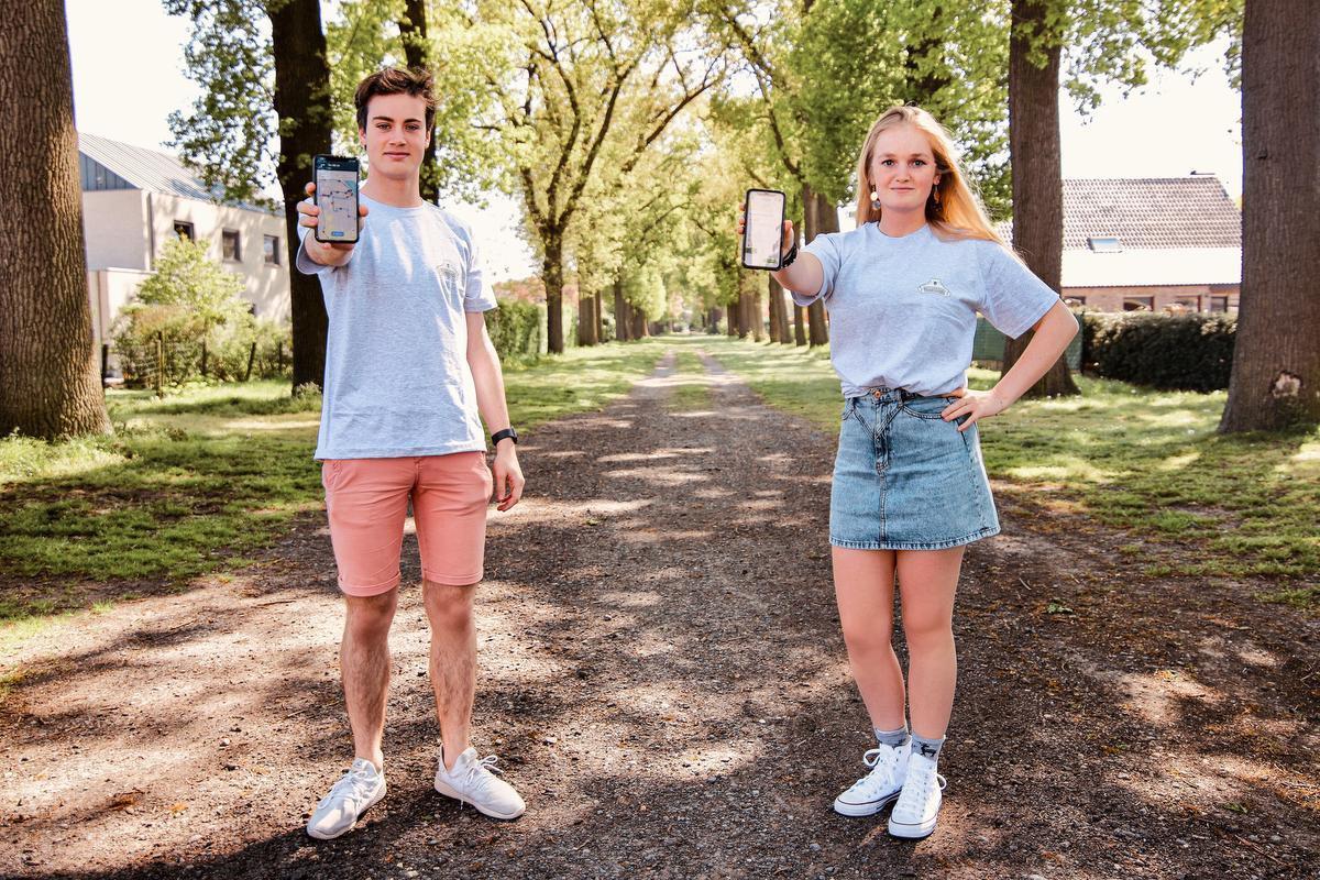 Lloyd en Maïté tonen de app waarop wandel- of fietsroutes staan.
