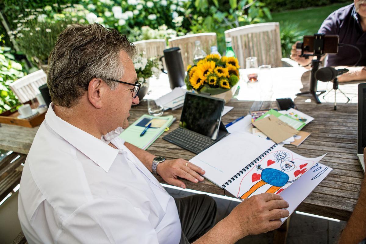 Dirk De fauw bekijkt een schriftje met tekeningen die kinderen uit de derde kleuterklas van basisschool Mozaïek voor hem maakten. (foto DC)