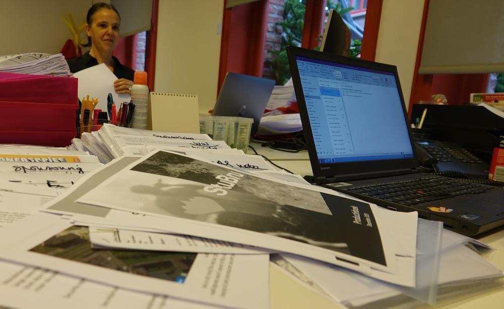 De bureau van Carine wordt de jongste weken overspoeld met documenten, plannen en draaiboeken.