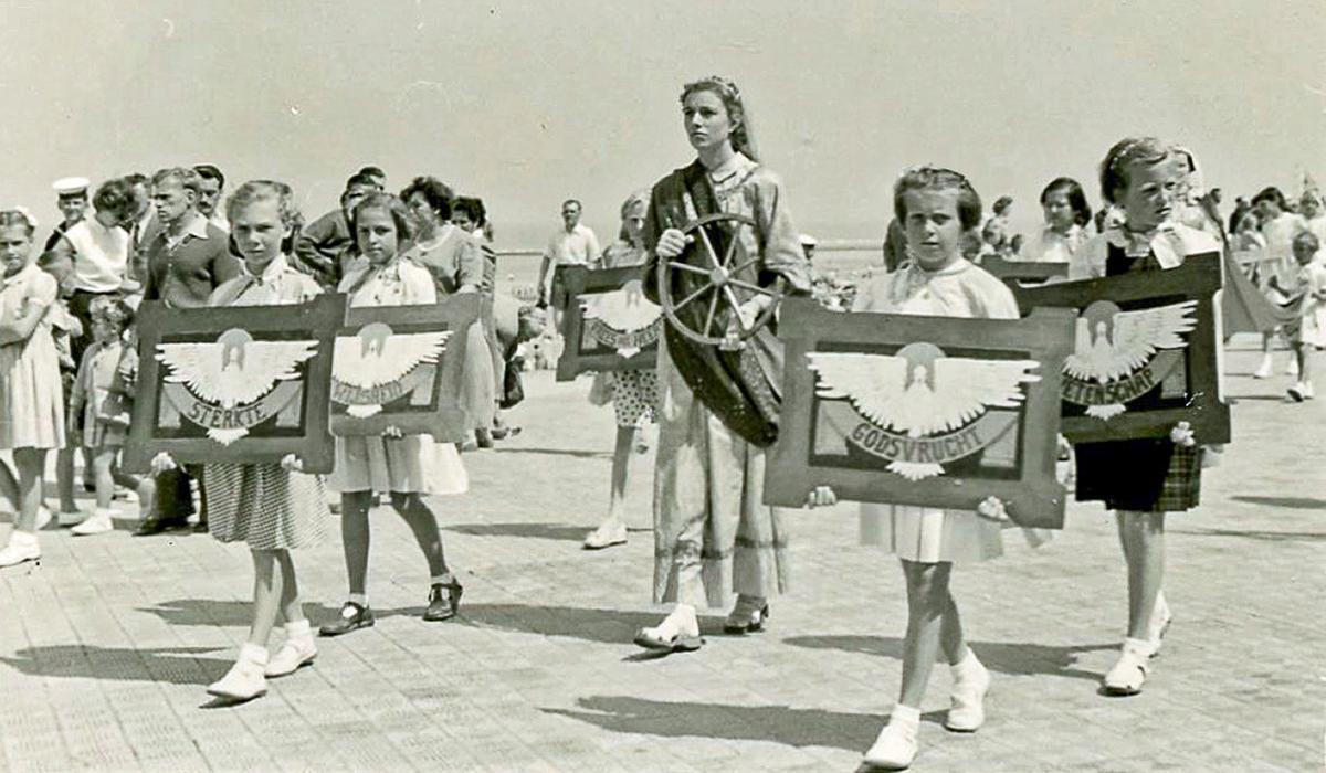 De processie trok op de eerste zondag van augustus door de straten van Middelkerke. Heel wat mensen plaatsten een Heilig Hartbeeld of een kruisbeeld aan het raam. Op de foto de groep Heilige Catharina met Marcelline Desseyn als de Catharina in 1950.
