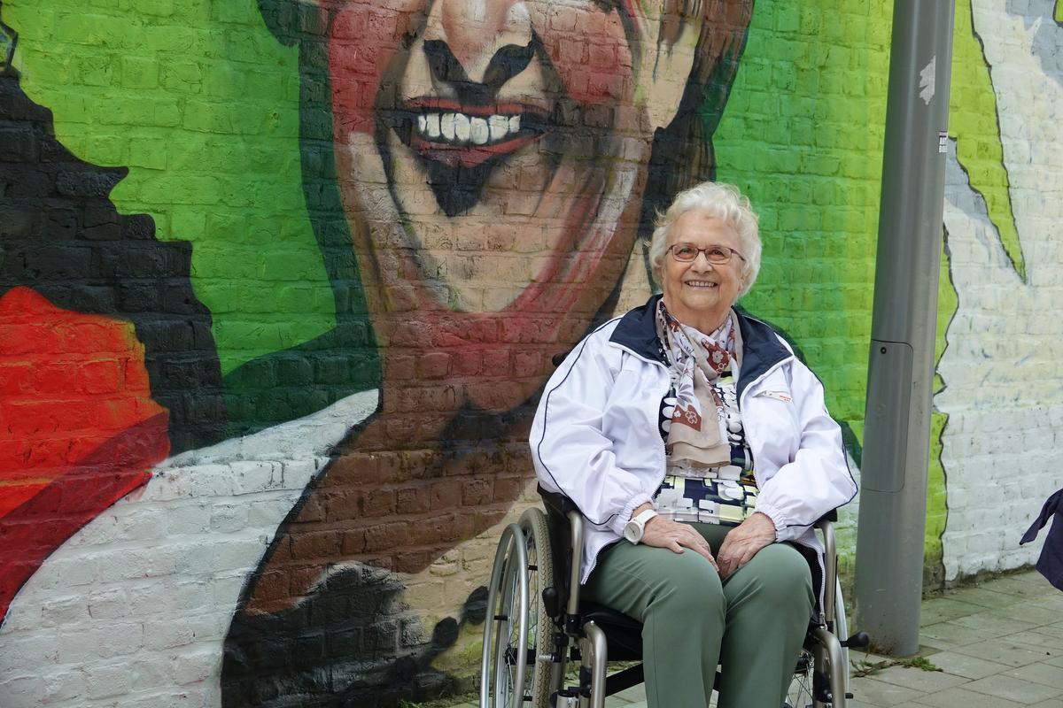 Christiane Cibouw poseert trots bij haar portret.