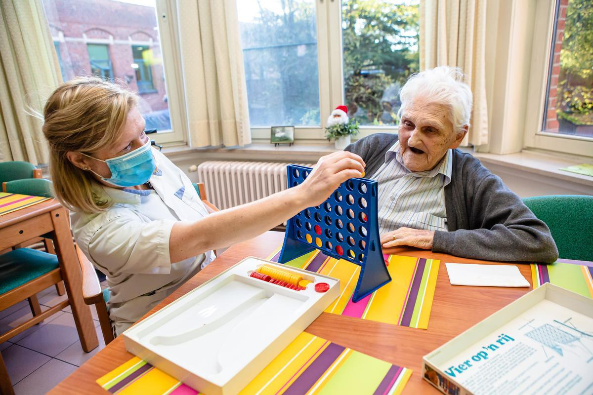 Zorgkundige Heidi Van Oost speelt een spelletje Vier op een rij met bewoner Raphael Annys.