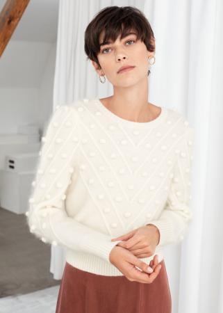 Witte trui met pofmouwen en pompons