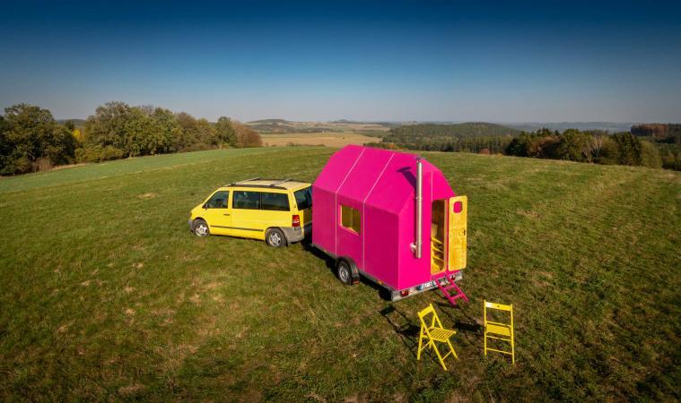 De caravan wordt op een aanhangwagen bevestigd.