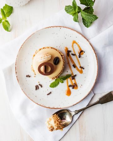 Kokosnootcheescakes met een frosting van chocolade en pinda's