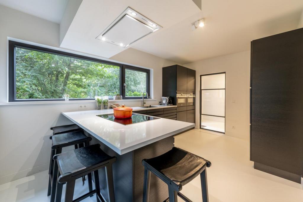 De zwarte keuken zorgt voor contrast in het sobere interieur.