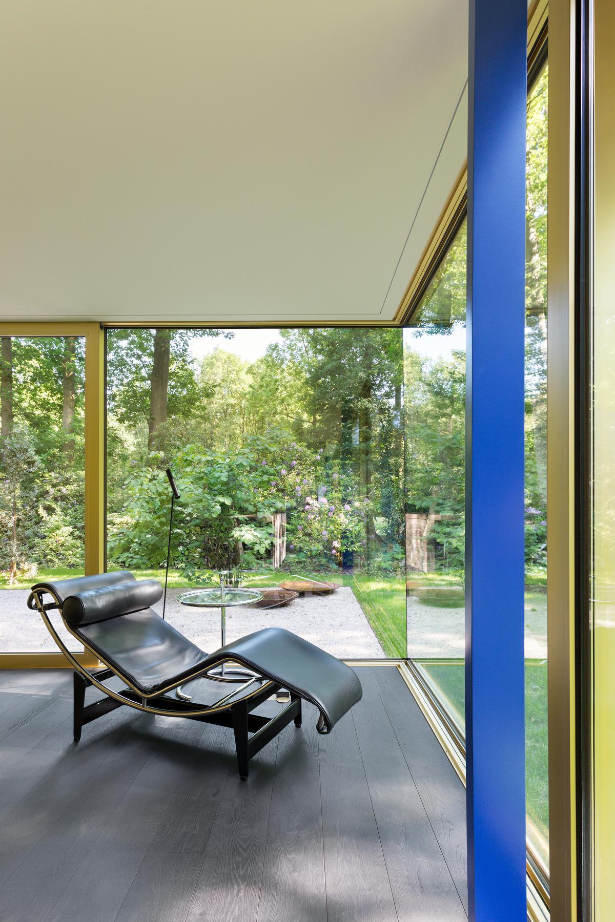 De leefruimte is volledig op de tuin georiënteerd, met glaspartijen van 16,5 meter lang. Gouden geanodiseerde raamprofielen omarmen de relaxte setting en de chaise longue van Le Corbusier.© Giulia Frigerio