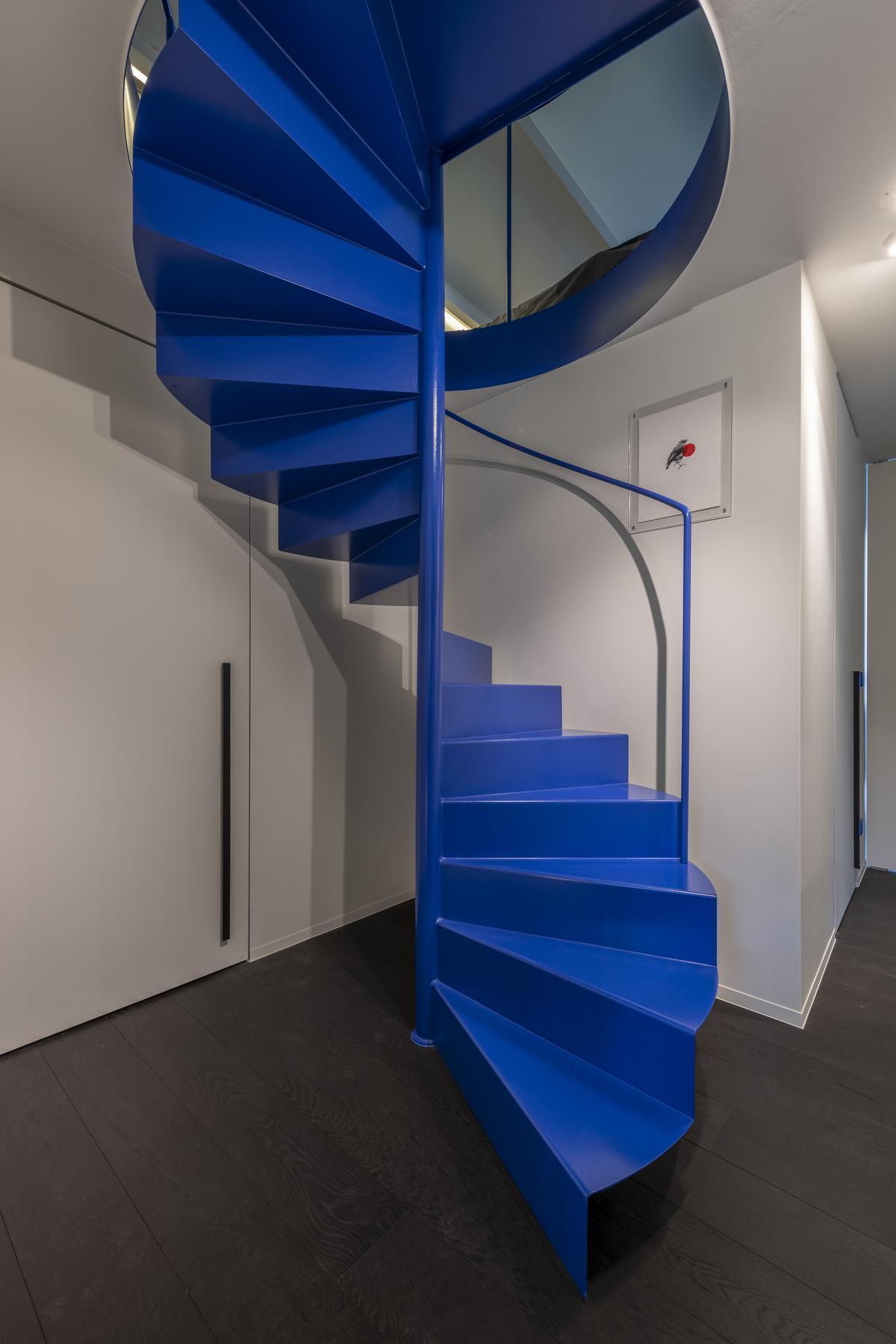 De typerende huiskleur Bleu Outremer herhaalt zich in de nachtzone met de wenteltrap, als wandkleur in de kinderkamer en in de originele Les Couleurs® Le Corbusier Jung-lichtschakelaars.© Pieter Clicteur