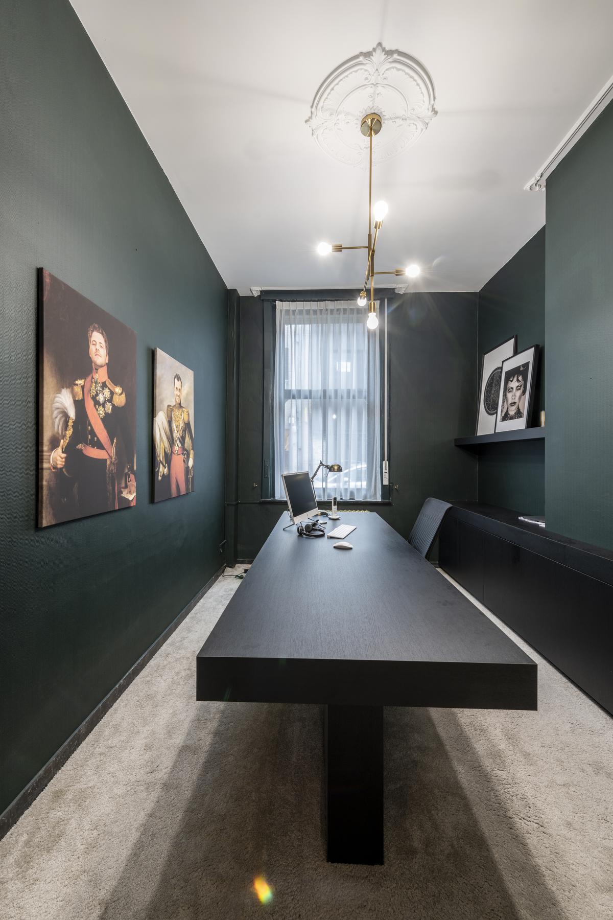 Het strakke bureau combineert mooi met de ornamenten aan het plafond, de kroonluchter en het zachte kamerbrede tapijt.© Pieter Clicteur